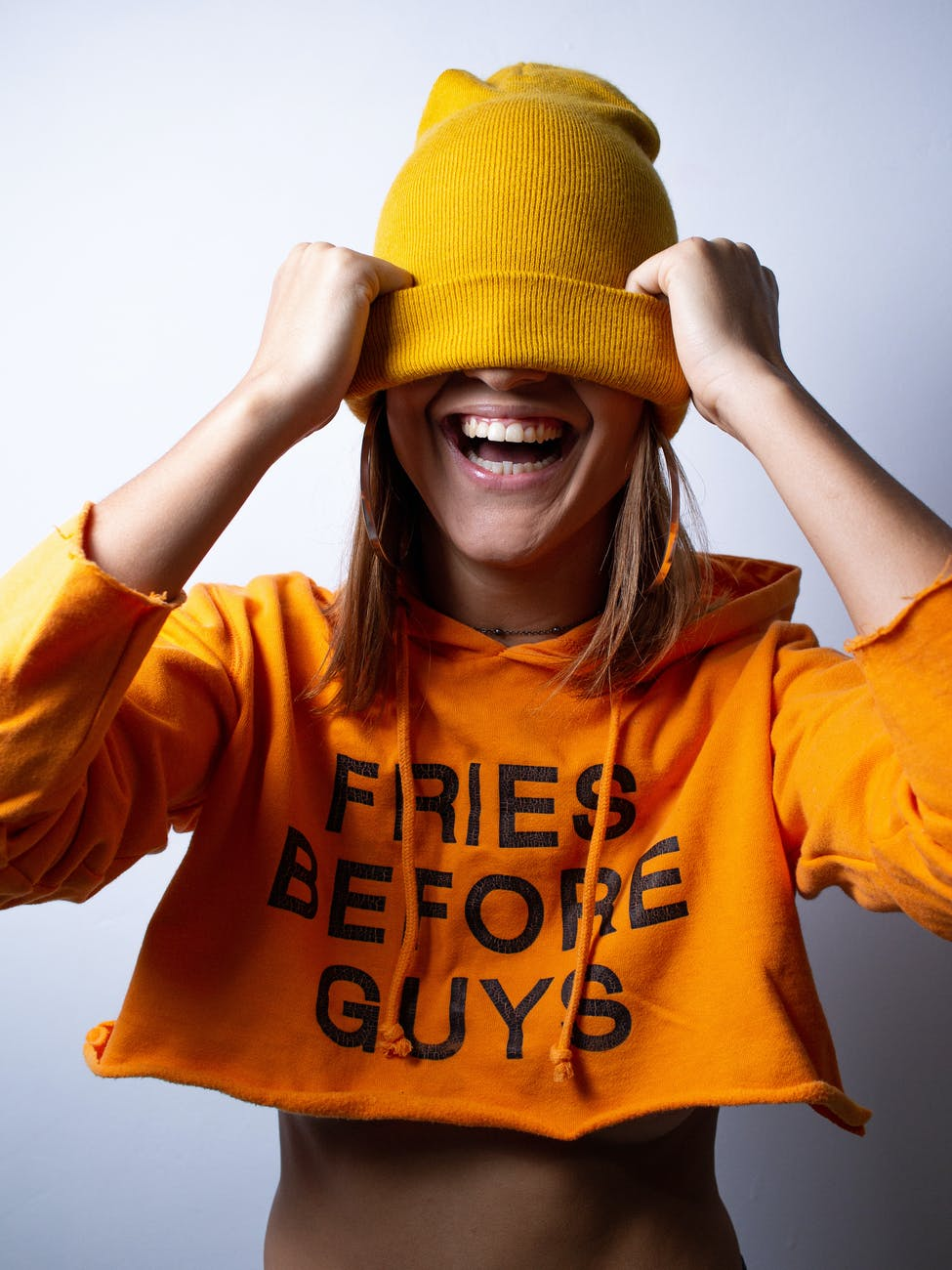 cheerful fit young lady covering eyes with hat and having fun