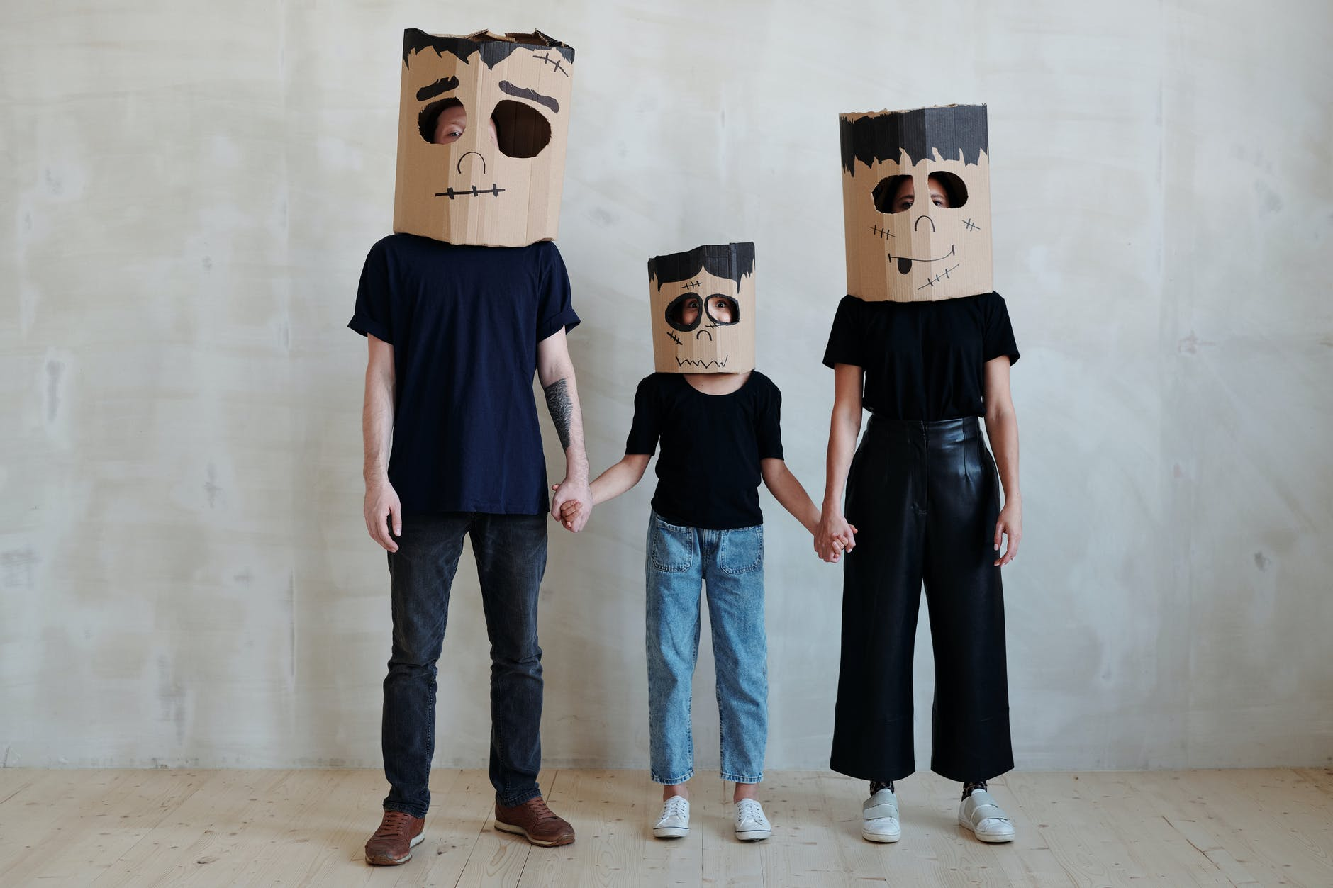 a family wearing diy cardboard box mask while holding each other s hands